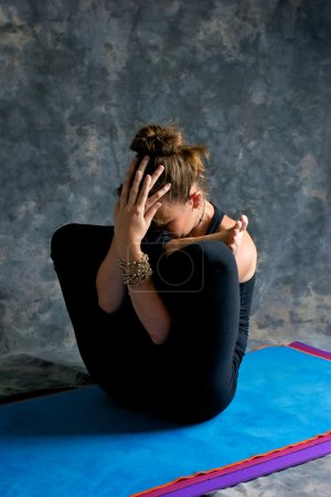 Woman doing yoga exercise Womb Embryo Posture or Garbha Pindasan