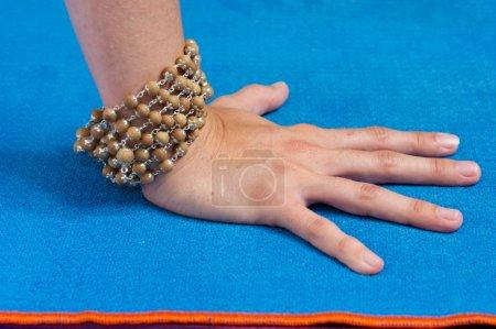Photo pour Gros plan de la main d'une femme en appuyant sur le tapis de yoga bleu avec garniture orange portant des perles de mala , - image libre de droit