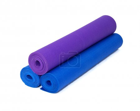 Three rolled yoga exercise mats stacked on white