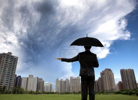 Businessman in dark suites with umbrella and watching storm
