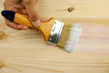 Wood texture, hand and paintbrush / covering by varnish