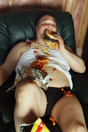 Photo for Photo of a fat couch potato eating a huge hamburger and watching television. Harsh lighting from the television illuminates the dark room. - Royalty Free Image