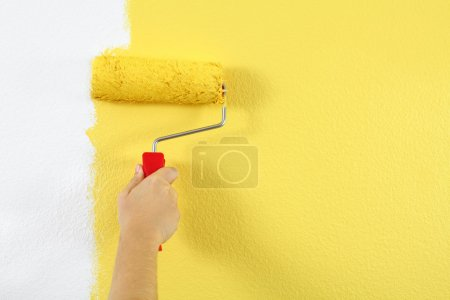 Photo for Photo of a female painting a wall with a roller and yellow paint. - Royalty Free Image