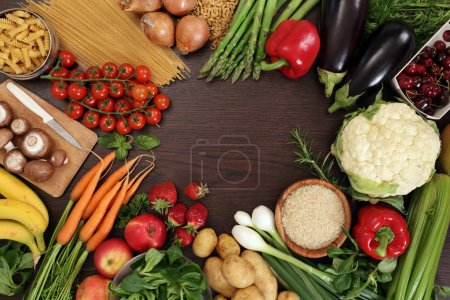Photo of a table top full of fresh vegetables, fru...