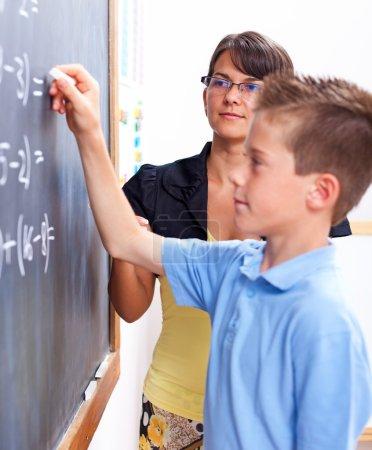 Boy writing on chalkboard in front of teacher