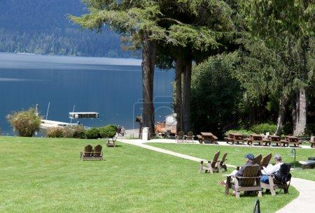 Photo pour Couple de retraités se détendre dans des chaises de jardin profiter du lac - image libre de droit
