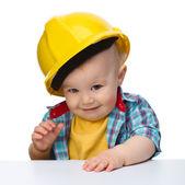 Cute little boy wearing oversized hard hat