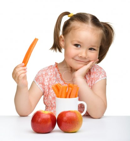 Photo for Cute little girl eats carrot and apples, isolated over white - Royalty Free Image