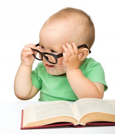 Photo pour Mignon petit enfant jouer avec le livre et les lunettes tout en étant assis à la table, isolé sur blanc - image libre de droit