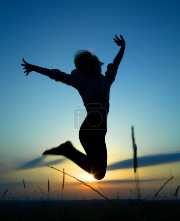 Silhouette of a girl jumping over sunset