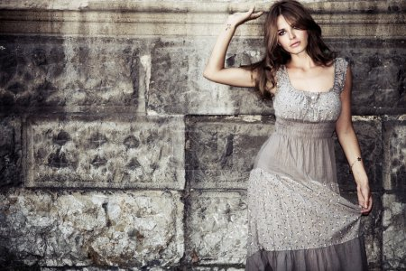 Photo for Young woman in summer dress against old stone wall, outdoor shot - Royalty Free Image