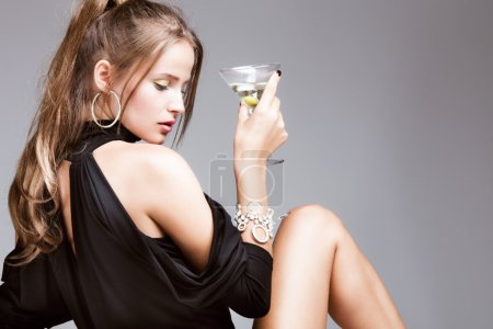 Photo for Young attractive woman with glass of martini, profile, studio shot - Royalty Free Image