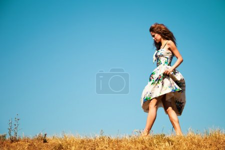 Woman walking through the grass, blue sky in background