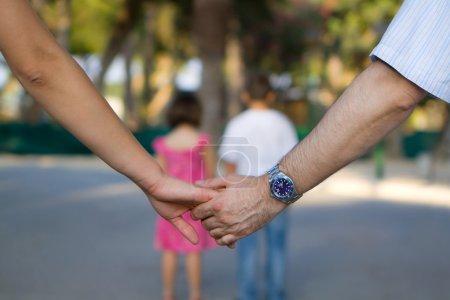 Photo pour Gros plan de main dans la main, deux enfants en arrière-plan - image libre de droit