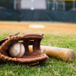 Old baseball, glove, and bat on field with base an...