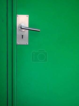 Metal door handle on green