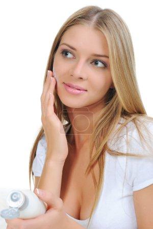 Beautiful woman applying cream on her cheek