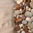 Colorful river stones on sand background...