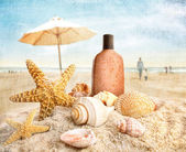 Suntan lotion and seashells on the beach