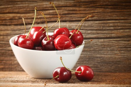 Red cherries in bowl on barn wood