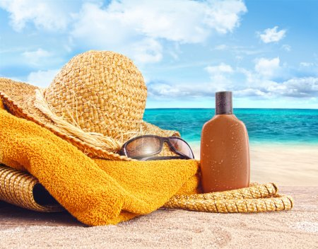 Photo for Suntan lotion, straw hat with towel at the beach - Royalty Free Image