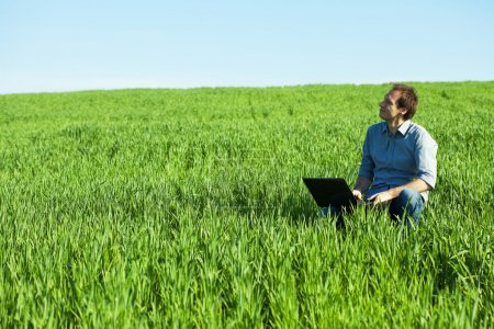 Photo for Young man using laptop in the field - Royalty Free Image