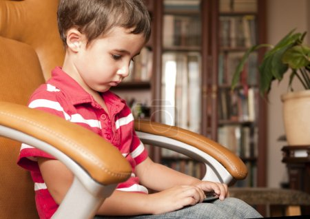 Little boy play smartphone game in leather chair