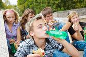 Teens eating sandwiches
