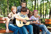 Teenagers in park playing guitar
