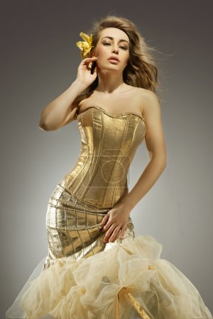 Photo for Elegant blonde beauty posing in a golden dress - Royalty Free Image