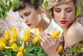 dos hermosas damas en un jardín de tulipán