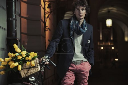 Young stylish guy next to bicycle