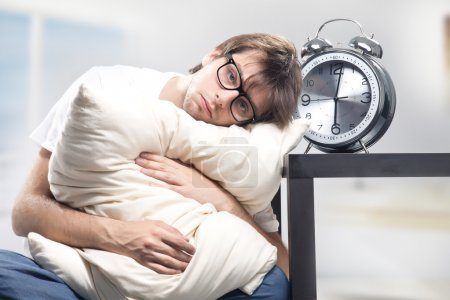 Photo for Sad man holding pillow and the clock - Royalty Free Image