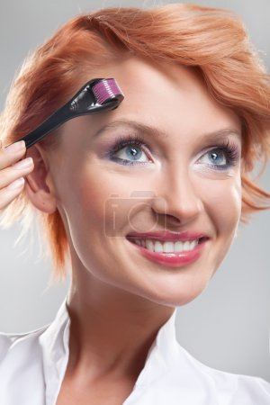 Beautiful smiling woman using dermaroller on face...