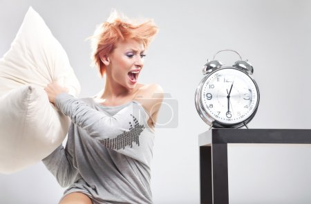 Cute woman destroying the clock with pillow
