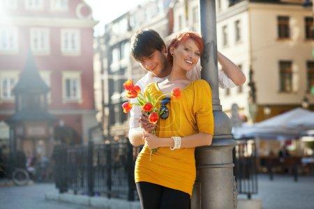 Photo pour Jeune couple avec des fleurs, à l'extérieur - image libre de droit