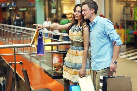 Foto de Joven mujer mostrando algo en el centro comercial - Imagen libre de derechos