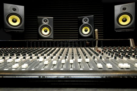Low angle shot of a mixing desk with yellow and bl...