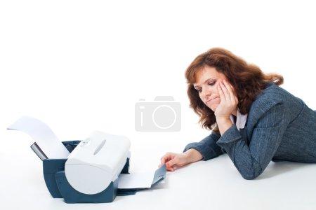 Foto de Mujer cansada que para esperar hasta el documento de impresión impresora, aislado en blanco - Imagen libre de derechos