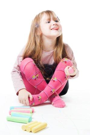 Photo pour Bonne petite fille avec des craies de couleur bâton sa langue sur - image libre de droit