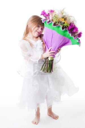 Photo pour Petite fille en robe blanche tenir bouquet de fleurs et joli sourire, isolé sur blanc - image libre de droit