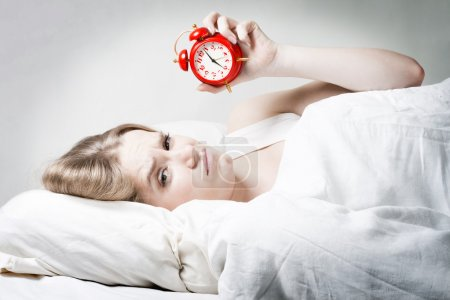 Photo pour Fatigué femme avec alarme dans sa main, ne pas obtenir suffisamment de sommeil - image libre de droit