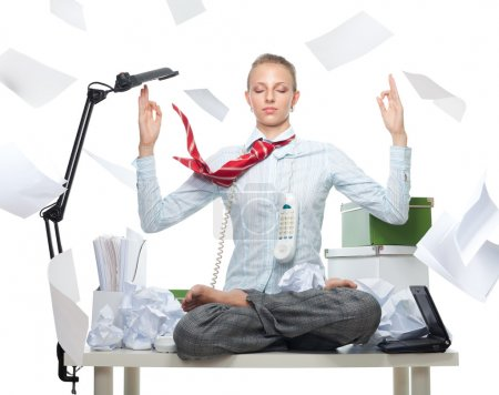 Photo for Calm business woman despite huge disorder on table and flying papers - Royalty Free Image
