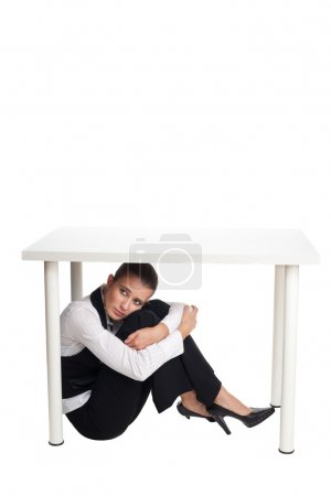 Depressed business woman hiding under a table