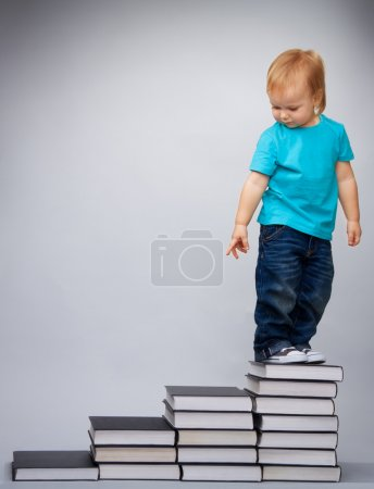 Photo pour Enfant au sommet du leader de l'éducation préscolaire constitué d'une pile de livres debout et regardant en arrière - image libre de droit
