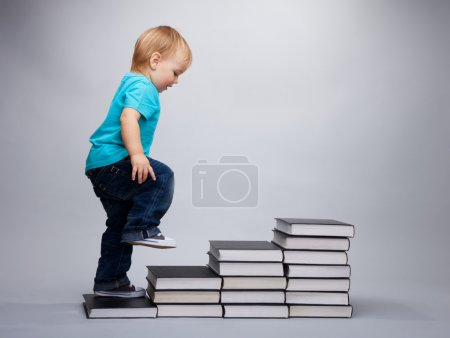 A toddler climbing on a steps made of books...