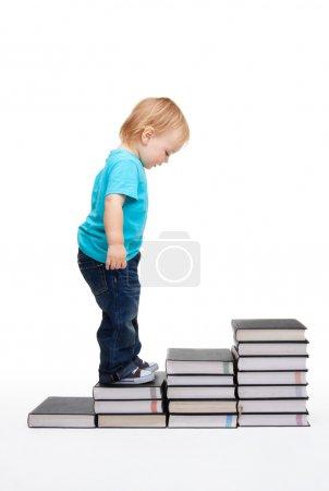 Photo pour Premiers pas de l'éducation - enfant sur les étapes faites de livres - image libre de droit
