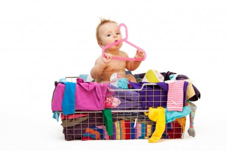 Photo for Baby in basket with clothes with hanger, isolated on white - Royalty Free Image