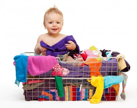 Photo for Happy smiling toddler in big basket with clothes - Royalty Free Image