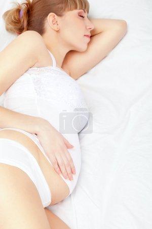 Foto de Hermosa mujer embarazada dormir en cama blanca - Imagen libre de derechos